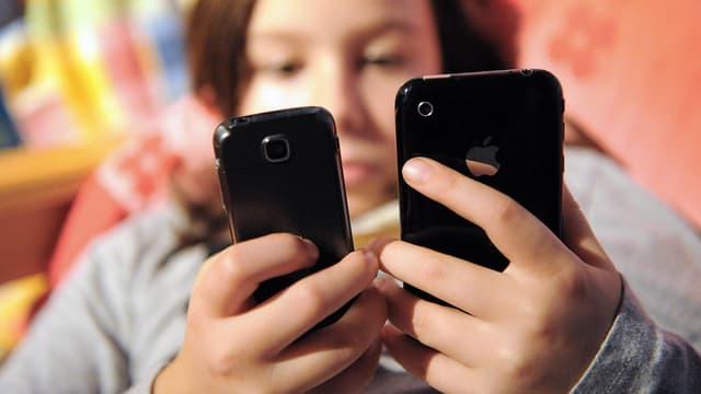 Une adolescente face à deux téléphones portables.
