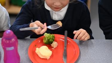 Photo d'illustration d'un enfant mangeant dans une cantine.