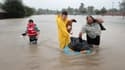 Des habitants de Houston se fraient un chemin dans leur quartier inondé, le 28 août 2017 à Houston (Texas).