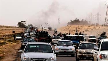 """Des insurgés et des civils fuient la ville d'Ajdabiah, dernier verrou avant le siège de l'insurrection, Benghazi. La ville est tombée mardi aux mains des forces de Mouammar Kadhafi, dirigeant que le G8 a menacé de conséquences """"dramatiques"""" mais contre qu"""