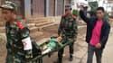 Des secouristes transportent un blessé après un tremblement de terre survenu dimanche dans le sud-ouest de la Chine.