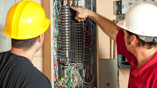 Des électriciens installent un panneau.