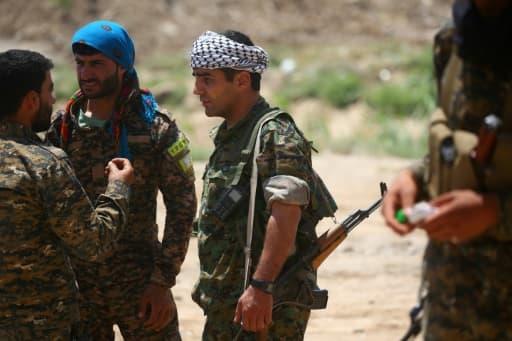 Des membres de la force kurdo-arabe soutenue par les Etats-Unis, le 11 juin 2017 dans un quartier de Raqa, fief du groupe Etat islamique (EI) en Syrie