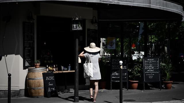Une femme devant un restaurant à Paris, le 27 mai 2020.