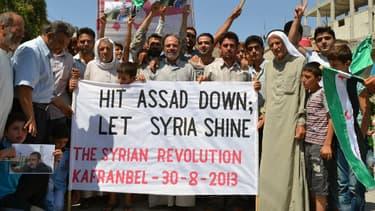 """L'opposition syrienne affichant le slogan: """"Hit Assad down, let Syria shine"""" (Faites tomber Assad, laissez briller la Syrie)"""