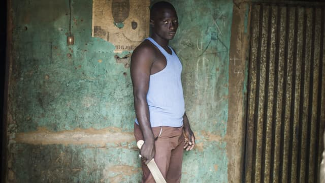 Un Malien pose devant son domicile avec une machette pour se protester contre les attaques des groupes djihadistes à Mopti, au Mali, en janvier 2013.