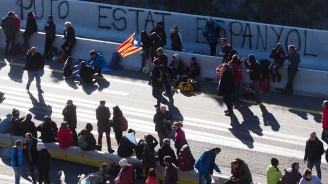 Un homme tient un drapeau de la Catalogne alors que des manifestants bloquent l'autoroute A9 à la frontière entre la France et l'Espagne, le 11 novembre 2019