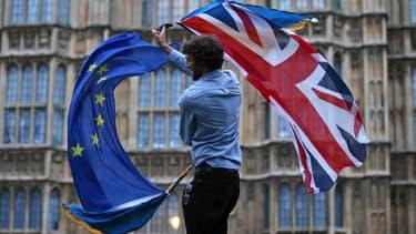 Un homme agitant un drapeau européen et britannique devant les chambres du Parlement