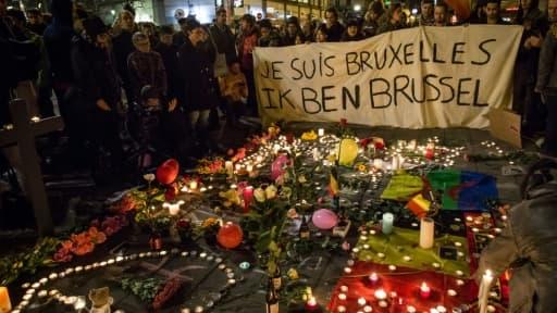 Des personnes rassemblées place de la Bourse à Bruxelles, le 22 mars 2016, devant un parterre de bougies, de fleurs et de messages en hommage aux victimes des attentats