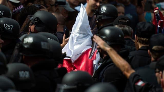 Un militant du KKK escorté par des policiers, le 8 juillet, à Charlottesville.