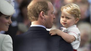 Le prince George dans les bras de son père lors du baptême de sa sœur, la princesse Charlotte, le 5 juillet 2015