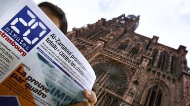 """Une personne lit le quotidien gratuit """"20 Minutes"""", le 15 septembre 2005 devant la cathédrale de Strasbourg, au lendemain du lancement de la huitième édition."""
