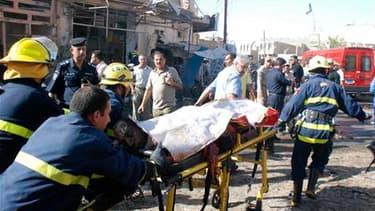 Evacuation d'une victime à Kut, à 150 km au sud-est de Bagdad. L'Irak a été lundi le théâtre d'une série de quatre attentats dont le plus grave perpétré dans la ville de Kut a fait au moins 37 morts et 68 blessés. /Photo prise le 15 août 2011/REUTERS/Jaaf