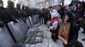 Des manifestants portant des icônes sont agenouillés face aux policiers anti-émeutes, le 24 janvier, à Kiev.