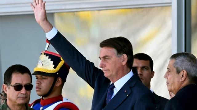 Le président brésilien Jair Bolsonaro (C) salue lors d'un défilé de véhicules militaires devant le palais du Planalto à Brasilia, le 10 août 2021