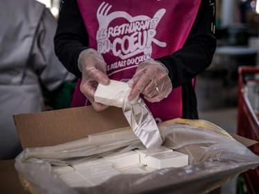 Des membres de l'association Les Restos du Cœur emballent des savons recyclés pour les bénéficiaires, le 24 mars 2021 à Givors