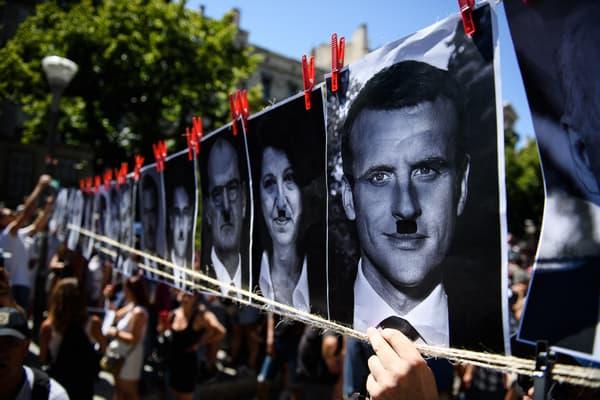 Des portraits d'Emmanuel Macron, Agnès Buzyn ou Jean Castex, retouchés avec la moustache d'Hitler, lors d'une manifestation à Marseille, le 17 juillet 2021.