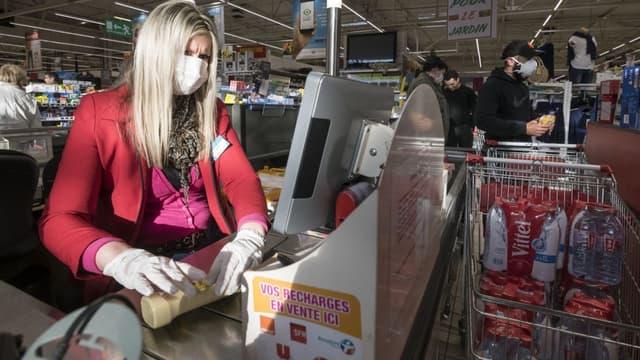 Une hôtesse de caisse équipée d'un masque de protection et de gants (photo d'illustration)
