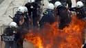 Policiers grecs cibles d'un cocktail molotov près du Parlement à Athènes, mercredi. Selon les services de pompiers, trois personnes sont mortes dans un immeuble incendié par des protestataires dans la capitale grecque lors de la manifestation contre le pl