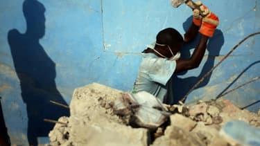 Des Haïtiens déblayent les ruines du tremblement de terre dans une rue de Port-au-Prince le 8 janvier 2011, un an après le séisme