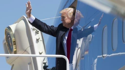 Le président américain Donald Trump salue lors de son embarquement à bord de l'avion présidentiel Air Force One, le 18 avril 2017 à la base aérienne d'Andrews, dans le Maryland