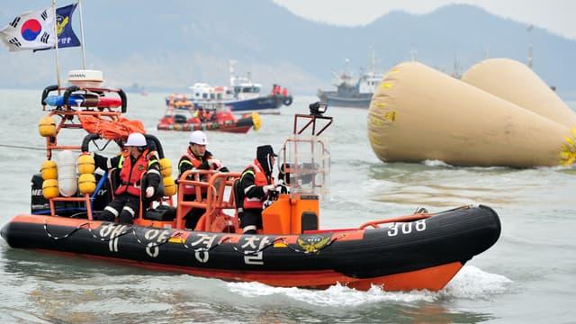 Des garde-côtes au-dessus de l'épave désormais submergée et localisée par des balises, le 19 avril.
