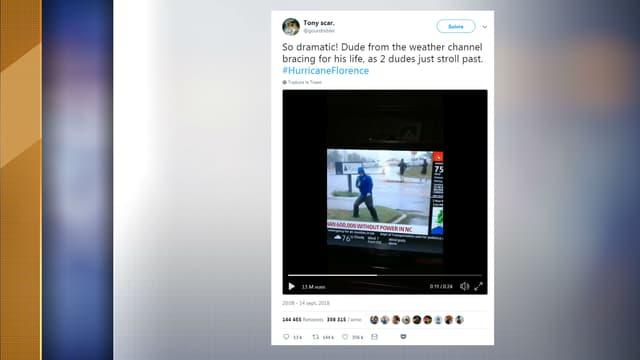 Un journaliste de The Weather Channel semble lutter contre le vent, alors que deux hommes marchent tranquillement derrière lui.
