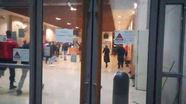 Plusieurs personnes, non masquées, applaudissent à la fin de l'évacuation de la faculté de droit par des hommes cagoulés et armés.
