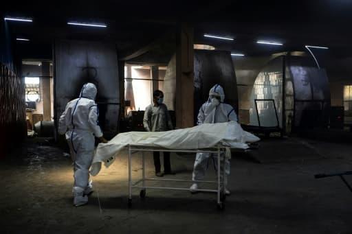 Des employés en combinaison protectrice près d'une civière où repose le corps d'une personne morte du coronavirus avant son incinération, le 3 juin 2020 au crématorium du site de Nigambodh Ghat à New Delhi