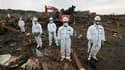 Policiers à la recherche de corps à Minamisoma, dans la préfecture de Fukushima, observant une minute de silence en hommage aux victimes du séisme et du tsunami qui a frappé le nord-est du Japon il y a un mois jour pour jour. Le gouvernement japonais a an