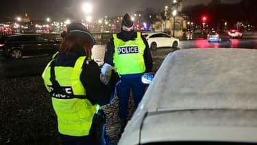 Des policiers contrôlent les passagers d'un véhicule place de la Concorde à Paris, le 16 janvier 2021, lors de l'entrée du couvre-feu avancé à 18 heures.
