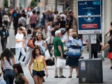 Des passants marchent près d'un panneau exigeant le port du masque à Nantes (France), le 17 juin 2021.