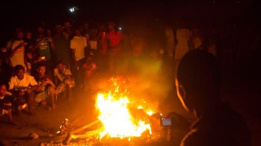 Une foule de gens filme le corps d'un Malgache jeté dans un brasier jeudi soir, selon l'AFP