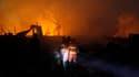 Pompiers à l'oeuvre sur le site d'une explosion dans la banlieue est de Rangoun, en Birmanie. Au moins 17 personnes sont mortes et 80 ont été blessées. /Photo prise le 29 décembre 2011/REUTERS/Soe Zeya Tun