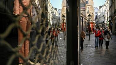 Des piétons dans une rue où les commerces non essentiels ont fermé, le 20 mars 2021 à Paris