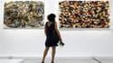"""""""Desert Bike, 1991"""" (à gauche) et """"White Handless, 1987"""" du plasticien Arman exposés au Centre Pompidou, à Paris. Une rétrospective de l'oeuvre de l'artiste français, connu pour ses violons en lamelles et autres carcasses de fauteuils calcinés, est présen"""