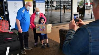 Un enfant accueille ses grands-parents de retour de Nouvelle-Zélande à l'aéroport de Manchester, dans le nord-ouest de l'Angleterre, le 31 juillet 2020
