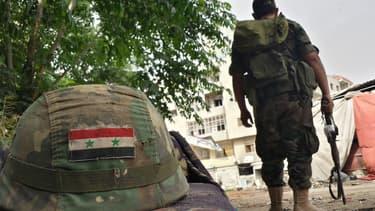 Un soldat syrien posté près d'un casque orné d'un drapeau syrien, à Homs, le 27 mai 2014.