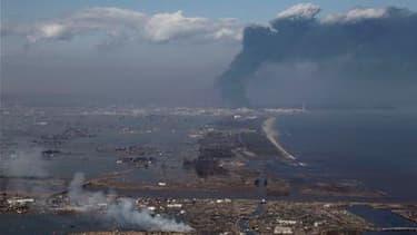 Colonne de fumée dans la ville de Sendai, au Japon. Vingt-cinq Français sont toujours recherchés dans cette région frappée vendredi par un très violent séisme, selon le porte-parole de l'ambassade de France. /Photo prise le 12 mars 2011/REUTERS/Jo Yong-Ha