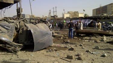 Sur les lieux d'un attentat à la voiture piégée à Bagdad. Une vague d'attaques contre des pèlerins chiites et la police a fait mercredi au moins 53 morts en Irak, où la majorité chiite célèbre une importante fête religieuse. /Photo prise le 13 juin 2012/R