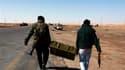 Combattants rebelles transportant des munitions sur le front à l'entrée ouest d'Ajdabiah. Paris et Londres, à l'avant-garde de l'intervention militaire dans le ciel libyen, ont pressé mardi l'Otan d'intensifier ses raids pour détruire les armes lourdes dé