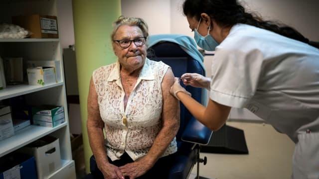 Camille Belo, infirmière dans l'Ehpad des Caselles à Bozouls dans l'Aveyron vaccine Emilienne Doutart, une résidente de 88 ans, contre la grippe saisonnière, le 14 octobre 2020