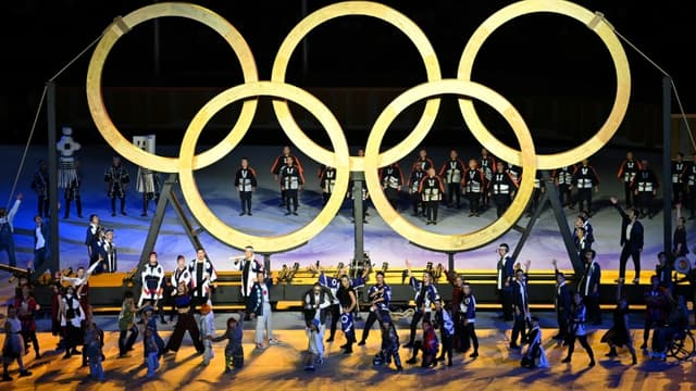 Des anneaux olympiques en bois sont hissés par des participants lors de la cérémonie d'ouverture des Jeux, le 23 juillet 2021 au Stade Olympique à Tokyo