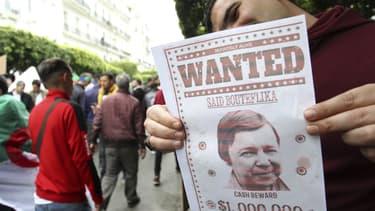 """Un manifestant algérien tenant une affiche """"WANTED Saïd Bouteflika"""", le 19 avril 2019 à Alger."""
