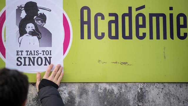 Un manifestant colle une affiche contre la réforme du BAC, à Nantes, lors de la grève du 14 février.