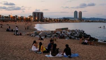 Des jeunes sur la plage de Barcelone à la tombée de la nuit, le 30 mai 2020 en Espagne