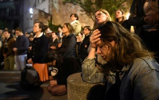 Parisiens et touristes chantant et priant pendant que Notre Dame est en flammes, à Paris, le 15 avril 2019