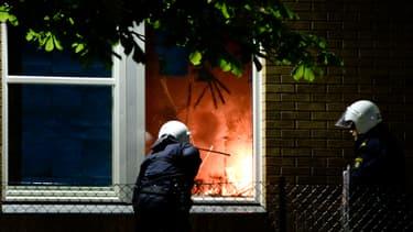 Des policier éteignent un début d'incendie dans une école de Tensta, dans la banlieue de Stockholm, où ont lieu pour la sixième nuit consécutive des émeutes.