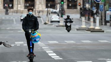 Un jeune homme utilisant une trottinette en libre-service de l'opérateur Dott, dans les rues de Paris.