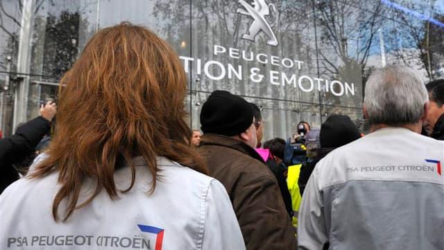 Salariés de PSA Peugeot Citroën devant le siège social du groupe, mardi à Paris. Le ministre du Travail et de l'Emploi, Xavier Bertrand, veut rencontrer prochainement le président du directoire de PSA Peugeot Citroën, Philippe Varin, pour lui demander des